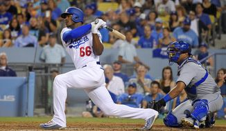 Los Angeles Dodgers' Yasiel Puig watches his solo home run in front of Kansas City Royals catcher Salvador Perez during the sixth inning of a baseball game, Friday, July 7, 2017, in Los Angeles. (AP Photo/Mark J. Terrill)