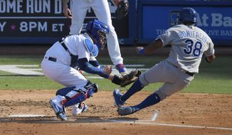 Kansas City Royals' Jorge Bonifacio, right, slides before being tagged out by Los Angeles Dodgers catcher Yasmani Grandal as he tried to score on a single by Eric Hosmer during the fourth inning of a baseball game, Saturday, July 8, 2017, in Los Angeles. (AP Photo/Mark J. Terrill)