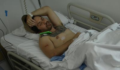 Bill Hillmann, a 35-year-old American from Chicago lies in a hospital bed after being gored at the San Fermin bull running Festival, in Pamplona, northern Spain, Saturday, July 8, 2017. Hillmann was in stable condition after televised images showed a bull thrusting its horn into a man's buttocks before flipping him into the street. Two Americans were gored and several other people were injured Saturday during the second running of the bulls at this year's San Fermin festival in the northern Spanish city of Pamplona, officials said.(AP Photo/Alvaro Barrientos)