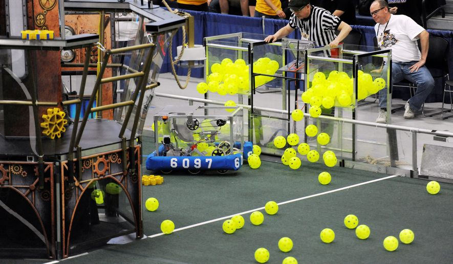 The Botcats team of Brethren, Michigan, released balls from containers during the FIRST Robotics District Competition in March. Teams of youths from nearly 160 nations have spent weeks building remote-controlled robots designed to maneuver through a variety of obstacles and compete to finish specific goals. (Associated Press)
