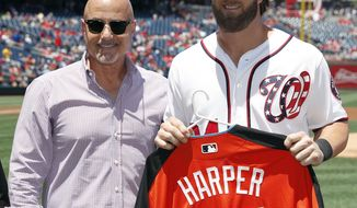 Washington Nationals general manager Mike Rizzo, left, stands with Washington Nationals right fielder Bryce Harper as he holds his National League All-Star jersey before a baseball game against the Atlanta Braves at Nationals Park, Sunday, July 9, 2017, in Washington. (AP Photo/Alex Brandon)