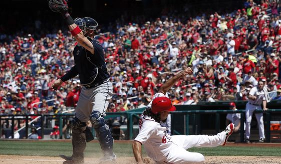 Washington Nationals third baseman Anthony Rendon scores on an RBI single by Chris Heisey, as Atlanta Braves catcher Tyler Flowers reaches to make the catch, during the fourth inning of a baseball game at Nationals Park, Sunday, July 9, 2017, in Washington. (AP Photo/Alex Brandon)