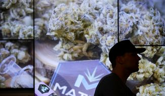 A man waits in line at The Source dispensary, Saturday, July 1, 2017, in Las Vegas. Recreational marijuana became legal in Nevada on Saturday. (AP Photo/John Locher)
