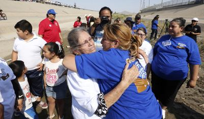"""In this Saturday, June 24, 2017 photo, Erendira Fraire, right, rushes over to greet her mother, Esperanza Mata Lara whom she had not seen in 21 years during a brief meeting in the Rio Grande riverbed as part of the """"Hugs Not Walls"""" family reunification event on the U.S-Mexico border. Fraire traveled from Chicago while her mother traveled from Gomez Palacio, Durango, Mexico for the four-minute encounter. (Rudy Gutierrez/The El Paso Times via AP)"""