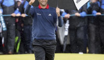 Spain's Jon Rahm acknowledges the crowd as he makes his way across the 18th green to win the Irish Open golf tournament at Portstewart Golf Club, Northern Ireland, Sunday July 9, 2017.  Rahm, one of the hottest young players in world golf, holed out from 150 yards for an eagle on No. 4 and strung together four straight birdies from No. 7 to turn what was promising to be a tight final day into a procession to win the tournament Sunday.  (Niall Carson/PA via AP)