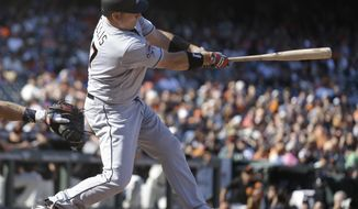 Miami Marlins' A.J. Ellis swings for a two-run home run off San Francisco Giants' George Kontos in the eleventh inning of a baseball game Sunday, July 9, 2017, in San Francisco. (AP Photo/Ben Margot)