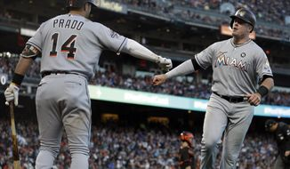 Miami Marlins' Justin Bour, right, is congratulated by Martin Prado after hitting a home run off San Francisco Giants' Jeff Samardzija during the fourth inning of a baseball game Saturday, July 8, 2017, in San Francisco. (AP Photo/Ben Margot)