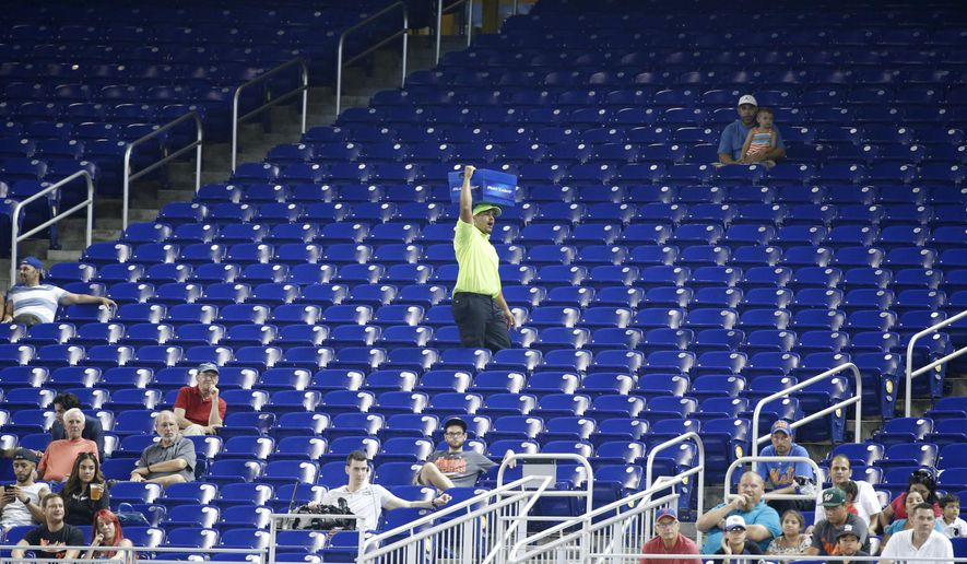 In this Tuesday, June 27, 2017, photo, a vendor walks through a section of mostly empty seats during the first inning of a baseball game between the Miami Marlins and the New York Mets at Marlins Park stadium in Miami. As the All-Star Game comes to Florida for the first time, the Marlins and Tampa Bay Rays continue their perennial struggles with attendance, raising the question: Does major league baseball belong in the state? (AP Photo/Wilfredo Lee)