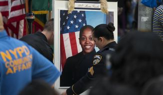 A portrait of slain New York police officer Miosotis Familia is placed on a podium before a tribute in her honor at the New York police department's 46th Precinct in the Bronx borough of New York, Saturday, July 8, 2017. Familia was shot to death early Wednesday, ambushed inside her command post by an ex-convict, who was later killed after pulling a gun on police. (AP Photo/Craig Ruttle)
