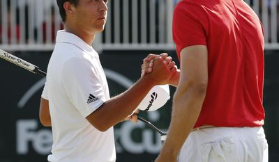 Xander Schauffele, left, shakes the hand of Jamie Lovemark, right, on the 18th green after winning the Greenbrier Classic PGA Tour golf tournament Sunday, July 9, 2017, in White Sulphur Springs, W.Va. (AP Photo/Steve Helber)