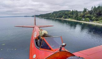 ADVANCE FOR SUNDAY JULY 9 AND THEREAFTER - In a Monday, July 3, 2017 photo, stunt pilot Vicky Benzing flys her 1940 Boeing Stearman biplane low along the Fox Island shore. From reaching speeds of nearly 470 miles per hour in a jet to skydiving or performing aerobatics, Benzing is at home in the sky.  (Peter Haley/The News Tribune via AP)