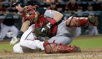Arizona Diamondbacks' Paul Goldschmidt is tagged out at the plate by Cincinnati Reds catcher Tucker Barnhart during the sixth inning of a baseball game, Sunday, July 9, 2017, in Phoenix. (AP Photo/Matt York)