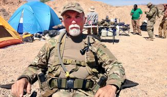 This Wednesday, April 16, 2014 photo shows Jerry DeLemus, of Rochester, N.H., talks, about heading a group of self-described militia members who have been camping on rancher Cliven Bundy's ranch near Bunkerville, Nev. Armed  backers of embattled rancher Cliven Bundy are still living along a state highway in southern Nevada, almost three weeks after an armed standoff halted U.S.  Bureau of Land Management plans to round up cattle he grazes on public land. The  BLM says Bundy owes $1.1 million in grazing fees and penalties. (AP Photo/Ken Ritter)