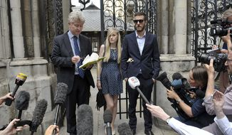 The parents of sick baby Charlie Gard, Connie Yates and Chris Gard, right, stand together as a statement is read by a family friend to the media, outside the High Court during an adjournment of their legal hearing to allow treated of their son with an experimental therapy, in London, Monday July 10, 2017. Charlie Gard is on life support at Great Ormond Street Hospital, and remains at the centre of a legal battle to allow the terminally ill infant to receive experimental treatment for his rare genetic disease, mitochondrial depletion syndrome. (Nick Ansell(/PA via AP)