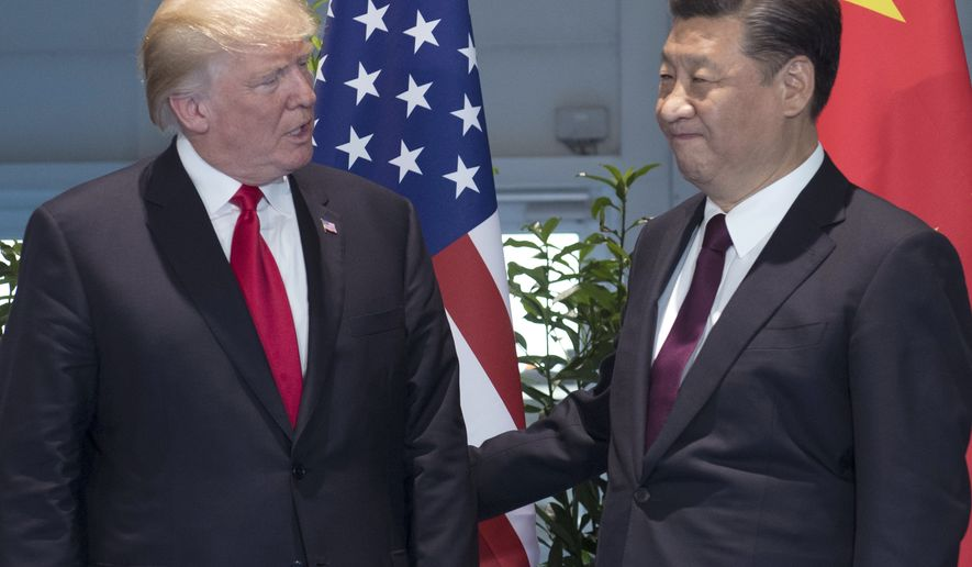 FILE - In this Saturday, July 8, 2017, file photo, U.S. President Donald Trump, left, and Chinese President Xi Jinping arrive for a meeting on the sidelines of the G-20 Summit in Hamburg, Germany. The United States apologized for mistakenly describing Xi as the leader of Taiwan, China said Monday, July 10, 2017. Chinese scholars said the mistake shows a lack of competence in the White House that is not conducive to healthy U.S.-China relations. (Saul Loeb/Pool Photo via AP, File)