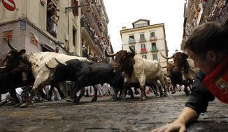 Revellers run in front of Fuente Ymbro's fighting bulls during the running of the bulls at the San Fermin Festival, in Pamplona, northern Spain, Monday, July 10, 2017. Revellers from around the world flock to Pamplona every year to take part in the eight days of the running of the bulls. (AP Photo/Alvaro Barrientos)