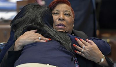FILE - In this April 17, 2017 file photo, Rep. Patricia Smith, D-Baton Rouge, gets a hug from Jada Delpit, granddaughter of Joe Delpit, who served in the House four years ago, during opening day at the Louisiana legislature in Baton Rouge, La. During a heated May debate on the Louisiana House floor about removing Confederate monuments, Smith urged her colleagues to reject a bill she argued had empowered white supremacists. Smith received 105 emails alone, almost all favoring a proposal by her Republican colleague Thomas Carmody that would have erected obstacles to tearing down such monuments. (Bill Feig/The Advocate via AP, Pool, File)