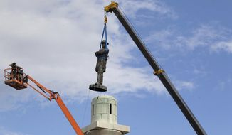 FILE- In this May 19, 2017 file photo, a statue of Confederate General Robert E. Lee is removed from Lee Circle in New Orleans. Lee's was the last of four monuments to Confederate-era figures to be removed under a 2015 City Council vote on a proposal by Mayor Mitch Landrieu. State Rep. Patricia Smith, a black Baton Rouge Democrat, received 105 emails alone, almost all favoring a proposal by her Republican colleague Thomas Carmody that would have erected obstacles to tearing down such monuments. (AP Photo/Scott Threlkeld, File)