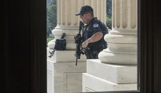 FILE - In this June 14, 2017 file photo, a Capitol Hill Police officer stands his post at the entrance to the House of Representatives on Capitol Hill in Washington. U.S. Capitol Police have investigated more threats to members of Congress in the first six months of the year than in all of 2016, says the chief law enforcement official for the House, as Majority Whip Steve Scalise remains hospitalized after a gunman opened fire at a baseball practice nearly a month ago.  (AP Photo/J. Scott Applewhite, File)