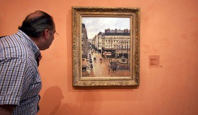 """FILE- This May 12, 2005 file photo shows an unidentified visitor viewing the Impressionist painting called """"Rue St.-Honore, Apres-Midi, Effet de Pluie"""" painted in 1897 by Camille Pissarro, on display in the Thyssen-Bornemisza Museum in Madrid. A Jewish woman's acceptance of a settlement from the German government for the Pissarro painting looted from her by the Nazis did not bar her grandchildren from suing to try to get the masterpiece back, a U.S. federal appeals court said Monday, July 10, 2017. (AP Photo/ Mariana Eliano, File)"""