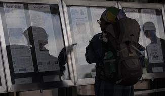 A woman, who did not wish to give her name, reads newspaper front pages displayed at the Newseum in Washington, Monday, July 10, 2017. News outlets are seeking permission from Congress for the right to negotiate jointly with Google and Facebook, two companies that dominate online advertising and online news traffic. (AP Photo/Carolyn Kaster)