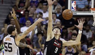 Houston Rockets' Zhou Qi, right, tries to block a shot by Phoenix Suns' Mike James, left, during the first half of an NBA summer league basketball game, Monday, July 10, 2017, in Las Vegas. (AP Photo/John Locher)