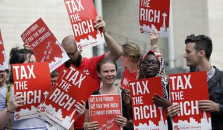 Demonstrators stand together as they wait for a Republican response to a new city income tax on the wealthy that was approved earlier by the Seattle City Council Monday, July 10, 2017, in Seattle. Seattle's wealthiest will become the only Washington state residents to pay an income tax under legislation unanimously approved by the City Council, a measure designed as much to raise revenue as to open a broader discussion about whether the wealthy pay their fair share. (AP Photo/Elaine Thompson)