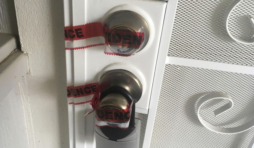 Red evidence tape covers part of the door leading to the condo where Ikaika Kang, a sergeant first class in the U.S. Army, lives in Waipahu, Hawaii, Monday, July 10, 2017. Kang is being held on terrorism charges after the FBI claims he tried to get secret military documents to the Islamic State group.  (AP Photo/Jennifer Sinco Kelleher)