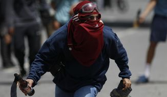 An anti-government protester holds a fire bomb during clashes with security forces on a day the opposition called for 10-hour road blocks in Caracas, Venezuela, Monday, July 10, 2017. Opposition protests demanding new elections and decrying triple-digit inflation, food shortages and worsening crime continue as President Nicolas Maduro pushes forward with his plan to draft a new constitution. (AP Photo/Ariana Cubillos)