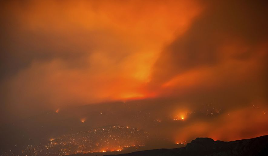 A wildfire burns on a mountain in the distance east of Cache Creek, British Columbia, early Monday, July 10, 2017. Wildfires barreled across the baking landscape of the western U.S. and Canada, destroying homes and forcing thousands of residents to flee. (Darryl Dyck/The Canadian Press via AP)