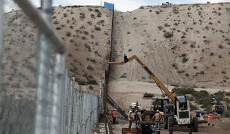 In this Nov. 10, 2016, file photo, workers continue work raising a taller fence in the Mexico-U.S. border area separating the towns of Anapra, Mexico, and Sunland Park, N.M. (AP Photo/Christian Torres, File)