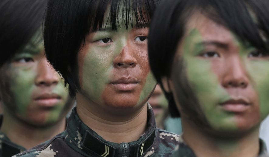 Female soldiers of Chinese People's Liberation Army (PLA) line up before demonstrating skills during an open day of Stonecutter Island naval base in Hong Kong, Saturday, July 8, 2017, to mark the 20th anniversary of Hong Kong handover to China. China's sole operating aircraft carrier arrived on its first port call to Hong Kong on Friday as part of efforts to stir patriotism amid commemorations of the city's handover from British to Chinese rule 20 years ago. (AP Photo/Kin Cheung)