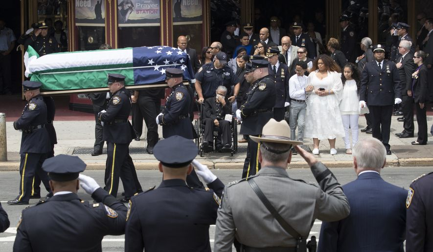 Police officers salute as slain New York City Police officer Miosotis Familia's mother Adriana Valoy, center, in wheel chair, son Peter, third from right, and daughter Genesis, and Delilah watch as her casket is carried from the World Changers Church, Tuesday, July 11, 2017, in the Bronx borough of New York. Familia was on duty in the Bronx when she was killed by Alexander Bonds, on July 5. Bonds was killed in a confrontation with police officers as he fled the scene.  (AP Photo/Mary Altaffer)
