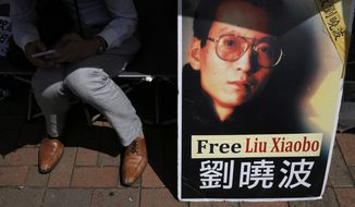 A protester displays a portrait of jailed Chinese Nobel Peace laureate Liu Xiaobo during a demonstration outside the Chinese liaison office in Hong Kong, Tuesday, July 11, 2017. Chinese doctors were working to treat critically ill Liu, as the government hardened its position against growing pleas to allow China's best-known political prisoner to leave for treatment overseas. (AP Photo/Kin Cheung)