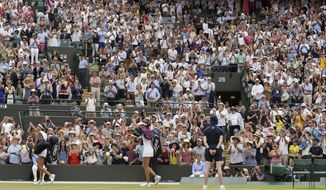 Britain's Johanna Konta, center, waves to spectators as she leaves the court after beating Caroline Garcia of France, left, in their Women's Singles Match on day seven at the Wimbledon Tennis Championships in London Monday, July 10, 2017. (AP Photo/Tim Ireland)
