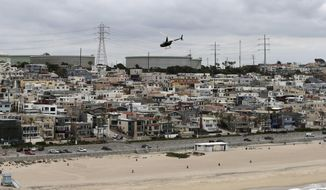 FILE - In this May 25, 2017 aerial photo, storage tanks from the Standard Oil Refinery in El Segundo, Calif., are seen behind the El Porto neighborhood in Manhattan Beach, Calif. A plan to extend California's signature climate initiative for another decade looks beyond cutting greenhouse gas emissions and takes aim at toxic air in the polluted neighborhoods around refineries and factories. (AP Photo/Reed Saxon, File)