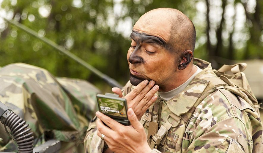 FILE -  In this July 3, 2017 file photo,  an American soldier gets ready for NATO's Saber Guardian exercises, smearing his face with camouflage paint near Gyor, 120 kilometers west of Budapest, Hungary. The NATO exercises officially launched on Tuesday, July 11, 2017, in Bulgaria, and they will also take place in Hungary and Romania. Preparation for the drills took place in the days before the official start of the exercises. (Csaba Krizsan/MTI via AP, File)