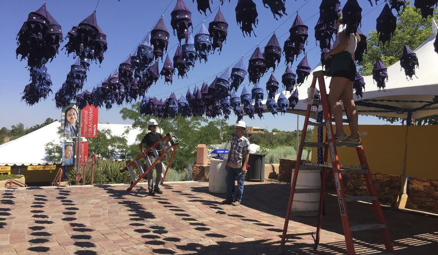 This July 10, 2017 photo workers hang lantern decorations at the entrance to the International Folk Art Market in Santa Fe, N.M. Organizers of the market say shifting U.S. policies on security and immigration have not hampered participation by artists from 53 countries, from Cuba to Jordan. In its 14th year, the annual bazaar is expanding its mission to highlight innovation and high-fashion within folk art traditions. (AP Photo/ Morgan Lee)