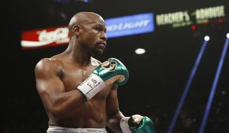 Floyd Mayweather Jr. fights Andre Berto (not shown) during their welterweight title in Las Vegas, in this Sept. 12, 2015, file photo. It's still early, but give Round 1 of the trash talk battle between Conor McGregor and Mayweather Jr. to the Irish MMA star. (AP Photo/Steve Marcus) ** FILE **