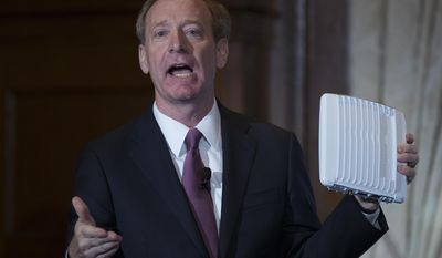 Microsoft President and Chief Legal Officer Brad Smith holds up an ACRS2 device by ADAPTRUM used in TV White Space communications as he speaks in Washington, Tuesday, July 11, 2017, about Microsoft's project to bring broadband internet access to rural parts of the U.S. (AP Photo/Carolyn Kaster)