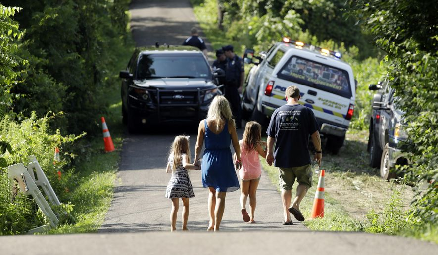 A family walks down a blocked off drive way, Monday, July 10, 2017, in Solebury, Pa. Authorities are chasing fast-developing leads in the search for four young men feared to be the victims of foul play, but said Monday that it could take days despite intense efforts centered on a large swath of farmland. (AP Photo/Matt Slocum)