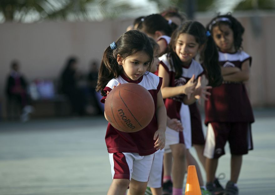 FILE- In this May 12, 2014 file photo, Saudi and expatriate girls practice basketball at a private sports club in Jiddah, Saudi Arabia. Saudi Arabia's Education Ministry said Tuesday July 11, 2017,  it will introduce physical education classes for girls in public schools next year, a decision that comes after years of calls by women across the kingdom demanding greater rights and greater access to sports. (AP Photo/Hasan Jamali, FILE)