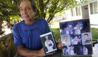 "In this Monday, July 10, 2017 photo, Clifford Kang, father of soldier Ikaika E. Kang, poses with photo of his son in Kailua, Hawaii.  Ikaika E. Kang, an active-duty U.S. soldier, was arrested over the weekend on terrorism charges that accuse him of pledging allegiance to the Islamic State group and saying he wanted to ""kill a bunch of people."" (Bruce Asato/The Star-Advertiser via AP)"
