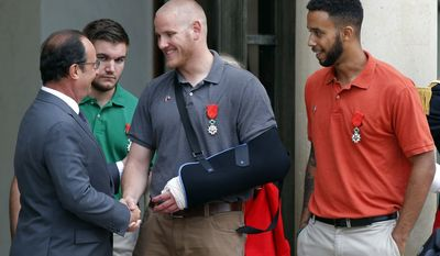 """FILE - In this Aug. 24, 2015 file photo, French President Francois Hollande bids farewell to U.S. Airman Spencer Stone as U.S. National Guardsman Alek Skarlatos of Roseburg, Ore., second from left, and Anthony Sadler, a senior at Sacramento State University in California, right, look on after Hollande awarded them with the French Legion of Honor at the Elysee Palace in Paris. The three Sacramento-area men who thwarted a terror attack on a French train in 2015 will play themselves in a Clint Eastwood-directed film about their heroic feat. Sadler, Skarlatos, and Stone will star in """"15:17 to Paris,"""" which began production this week. (AP Photo/Michel Euler, File)"""