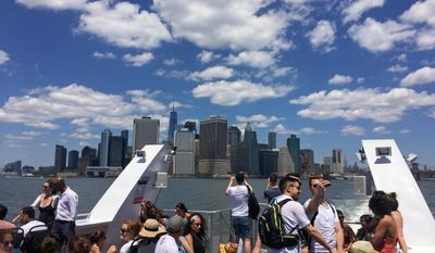This July 9, 2017 photo shows a view of One World Trade and other skyscrapers as seen from a ferry boat leaving Lower Manhattan and heading to Rockaway Beach in the Queens borough of New York. The new ferry is a scenic way to access the Rockaways, a favorite local summertime destination. (AP Photo/Beth J. Harpaz)