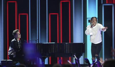 """In this March 12, 2016, file photo, Charlie Puth, left, and Wiz Khalifa perform at the Kids' Choice Awards at The Forum in Inglewood, Calif. Wiz Khalifa's video for """"See You Again"""" featuring Puth is now the site's most-watched video ever, with more than 2.896 billion views Tuesday, July 11, 2017. (Photo by Matt Sayles/Invision/AP, File)"""