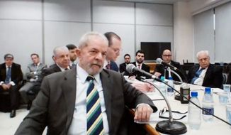 Former President Luiz Inacio Lula da Silva (center) was convicted of corruption Wednesday and sentenced to a decade in jail. Silva will remain free pending appeal. (Associated Press)