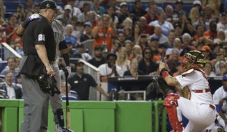 American League's Cleveland Indians outfielder Michael Brantley poses for a photo with home plate umpire Joe West, as National League catcher Yadier Molina, right, takes a photo, during the MLB baseball All-Star Game, Tuesday, July 11, 2017, in Miami. (AP Photo/Alan Diaz)