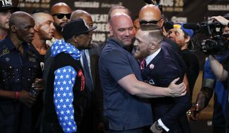 UFC president Dana White, center, intervenes as Floyd Mayweather Jr., left, and Conor McGregor exchange words during a news conference at Staples Center Tuesday, July 11, 2017, in Los Angeles. The two will fight in a boxing match in Las Vegas on Aug. 26. (AP Photo/Jae C. Hong)