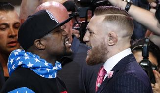 Floyd Mayweather Jr., left, and Conor McGregor exchange words during a news conference at Staples Center Tuesday, July 11, 2017, in Los Angeles. The two will fight in a boxing match in Las Vegas on Aug. 26. (AP Photo/Jae C. Hong)